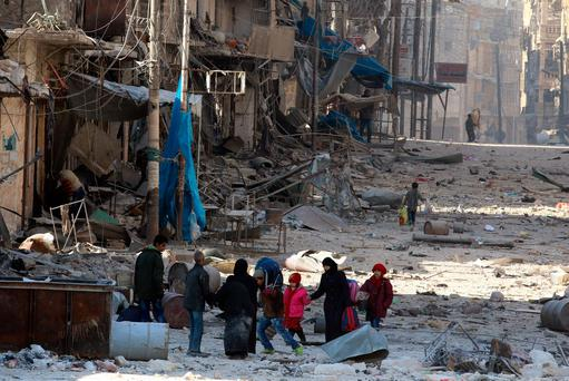 Syrians walk over rubble while carrying their belongings as they flee clashes between government forces and rebels in Tariq al-Bab and al-Sakhour neighborhoods of east Aleppo. Photo: Reuters