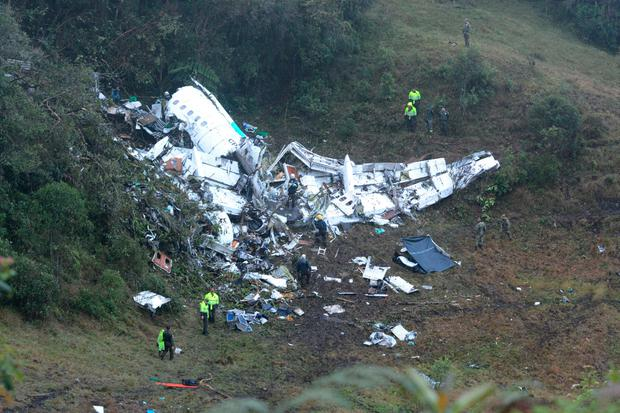 Police officers and rescue workers search for survivors around the wreckage of a chartered airplane that crashed in La Union, a mountainous area outside Medellin, Colombia, Wednesday , Nov. 30, 2016. (AP Photo/Luis Benavides)