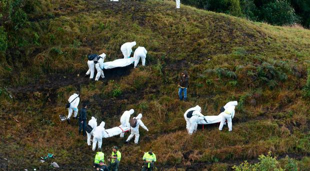 Rescue workers carry the bodies of victims of an airplane that crashed in a mountainous area outside Medellin, Colombia. The plane was carrying the Brazilian first division soccer club Chapecoense team that was on it's way for a Copa Sudamericana final match against Colombia's Atletico Nacional. (AP Photo/Luis Benavides)