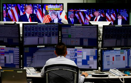 An employee of a foreign exchange trading company works near monitors showing US President-elect Donald Trump speaking on TV in Tokyo