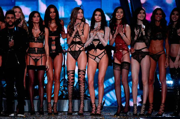 Canadian singer/songwriter The Abel Tesfaye a.k.a The Weeknd (L) cheer alongside Victoria's Secret Angels US model Martha Hunt, Portuguese model Sara Sampaio, Brazilian model Lais Ribeiro, US model Gigi Hadid, US model Kendall Jenner, Chinese model Liu Wen, Chinese model Sui He, Brazilian model Izabel Goulart and Chinese model Ming Xi during the 2016 Victoria's Secret Fashion Show at the Grand Palais in Paris