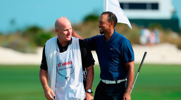 Tiger Woods (R) of the United States celebrates with caddie Joe LaCava (L) as he walks off the 18th green