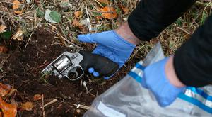 A Garda forensics officer removes a gun from near the scene Photo: Brian Lawless