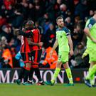 Bournemouth's Benik Afobe celebrates with Callum Wilson and Ryan Fraser after the game as Liverpool's Jordan Henderson and Lucas Leiva look dejected