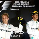 Nico Rosberg celebrates on the podium in Abu Dhabi after sealing the world championship as team-mate Lewis Hamilton applauds through gritted teeth. Photo: David Davies/PA