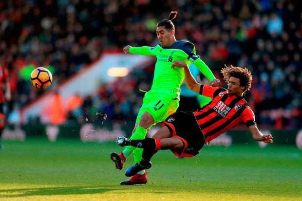 Liverpool's Roberto Firmino and Bournemouth's Nathan Ake battle for the ball. Photo: PA