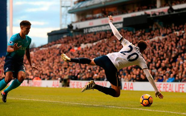 Tottenham Hotspur's Dele Alli (right) goes down in the penalty area after a tangle with Swansea City's Kyle Naughton (left)