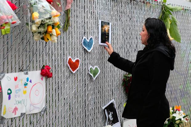 Janet Lino, 35, who lives in the neighborhood, looks at a sidewalk memorial near the burned warehouse following the fatal fire in the Fruitvale district of Oakland, California, U.S. December 5, 2016. REUTERS/Lucy Nicholson