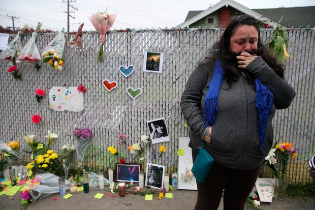 Danielle Boudreaux, 40, who knew Derick Ion Almena and his children and went to the Ghost Ship many times, cries at a sidewalk memorial near the burned warehouse following the fatal fire in the Fruitvale district of Oakland, California, U.S. December 5, 2016. REUTERS/Lucy Nicholson