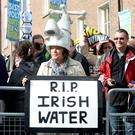 A woman holds a sign at a water protest outside the Dáil back in March. Photo: Justin Farrelly