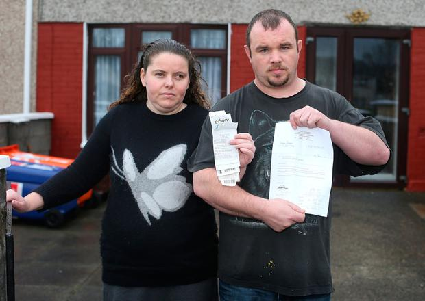 Simon Parsons and Michelle Daly holding a letter they received before their car was seized by the Dublin County Sheriff for non payment of Tolls. Picture credit; Damien Eagers