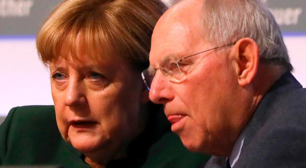 German Chancellor Angela Merkel talks to German finance minister Wolfgang Schaeuble at the CDU party convention in Essen yesterday. Photo: Kai Pfaffenbach/Reuters
