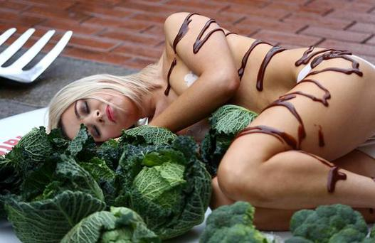 Katie Doherty pictured lying on a giant Christmas plate complete with to-scale cutlery, Brussels sprouts, and gravy.
