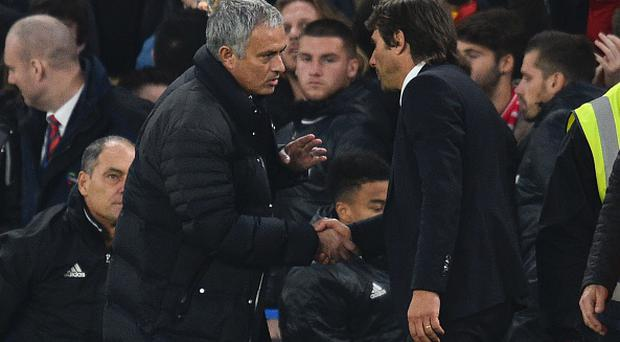Manchester United's Jose Mourinho (L) shakes hands with Antonio Conte