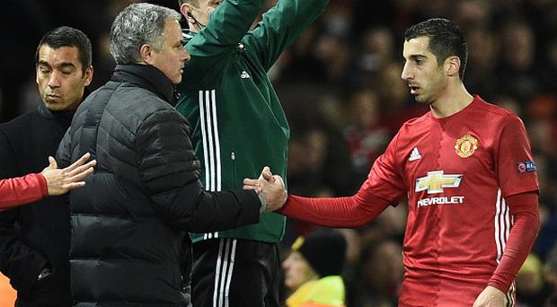 Manchester United's Armenian midfielder Henrikh Mkhitaryan (R) shakes hands with Manchester United's Portuguese manager Jose Mourinho (L) as he is substituted during the UEFA Europa League group A football match between Manchester United and Feyenoord at Old Trafford stadium in Manchester, north-west England, on November 24, 2016. / AFP / Oli SCARFF