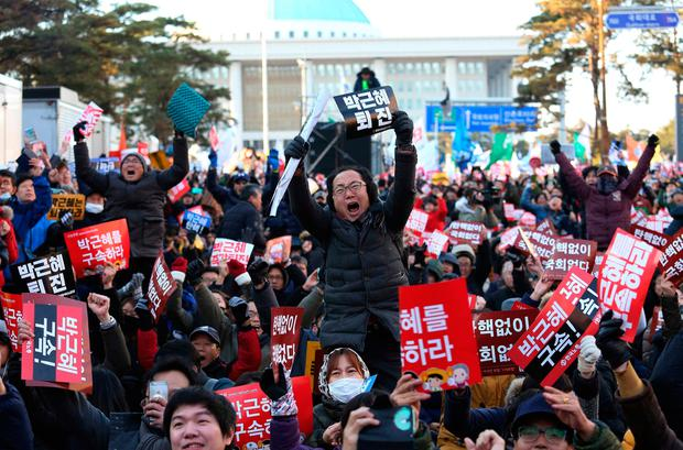 Protesters celebrate after hearing the President Park Geun-hye's impeachment in front of the National Assembly in Seoul. (AP Photo/Ahn Young-joon)