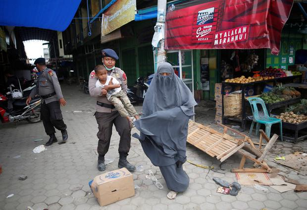 A police officer carries a child as he helps a woman leave a covered market, after an aftershock was felt, following this week's strong earthquake in Meureudu, (Photo: REUTERS/Darren Whiteside)