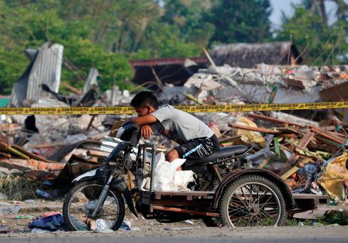 A cart driver rests in front of a building which collapsed following this week's strong earthquake in Pidie Jaya, Aceh province, Indonesia, December 10, 2016. REUTERS/Darren Whiteside