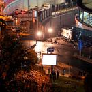 Horror: Fire fighters and police cover the dead lying in the debris at the site of a car bomb explosion outside the stadium of football club Besiktas in central Istanbul last night