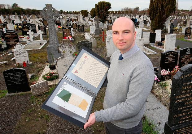 Historian Conor Dodd at Glasnevin Cemetery with the remnants of the Jacob's 1916 flag. Photo: Frank McGrath