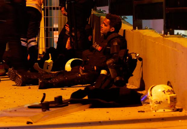 Wounded police officers are helped after one of the blasts. REUTERS/Murad Sezer