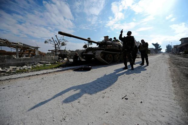 Forces loyal to Syria's President Bashar al-Assad walk past a tank in the government held Sheikh Saeed district of Aleppo, during a media tour, Syria December 12, 2016. REUTERS/Omar Sanadiki