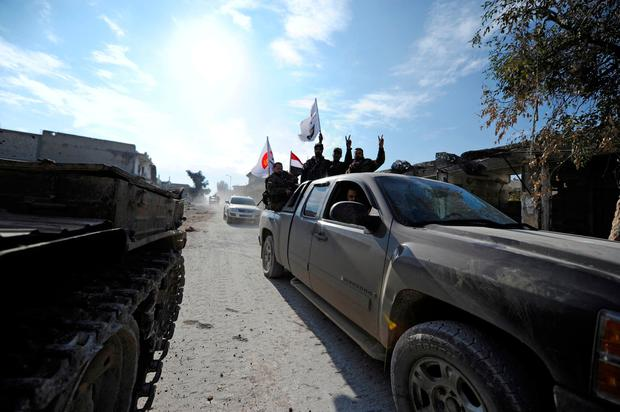 Forces loyal to Syria's President Bashar al-Assad gesture as they ride on a pick-up truck in the government held Sheikh Saeed district of Aleppo, during a media tour, Syria December 12, 2016. REUTERS/Omar Sanadiki