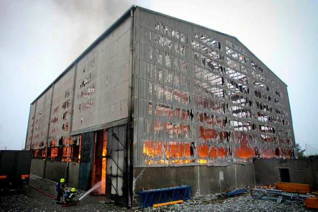 Firefighters tackle the fire at the old warehouse that used to house the Asgard II training ship. Photo: Garry O'Neill