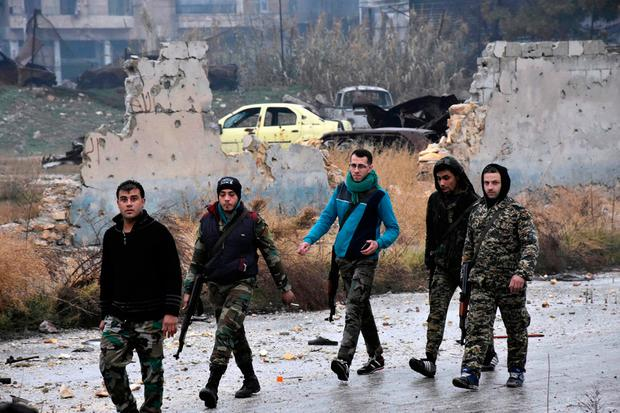 This photo released by the Syrian official news agency SANA, shows Syrian troops and pro-government gunmen marching through the streets of east Aleppo, Syria. (SANA via AP)