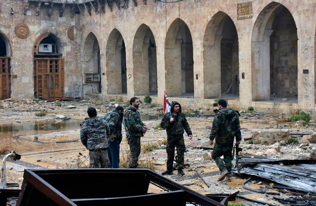 This photo released by the Syrian official news agency SANA, shows Syrian troops and pro-government gunmen marching walk inside the destroyed Grand Umayyad mosque in the old city of Aleppo, Syria, Tuesday, Dec. 13, 2016. (SANA via AP)