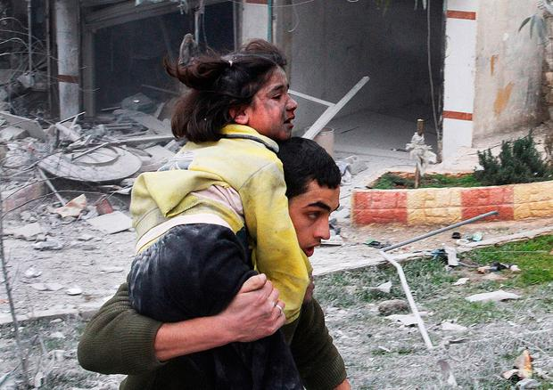 A Syrian man carries his sister who was wounded after a government airstrike hit the neighborhood of Ansari, in Aleppo, Syria, Sunday, Feb. 3, 2013. (AP Photo/Abdullah al-Yassin, File)