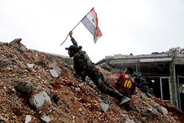 A Syrian army soldier places a Syrian national flag during a battle with rebel fighters at the Ramouseh front line, east of Aleppo, Syria, Monday, Dec. 5, 2016. (AP Photo/Hassan Ammar, File)