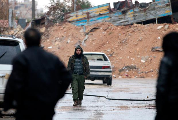 Free Syrian Army fighters walk along a street in a rebel-held besieged area of Aleppo, Syria December 14, 2016. REUTERS/Abdalrhman Ismail