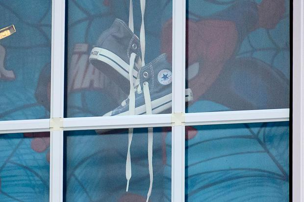 Spider-Man curtains and a pair of small shoes hang in the window of a property on The Fairway in Ruislip where the bodies of a woman and a boy were discovered. Photo: Ben Cawthra/LNP