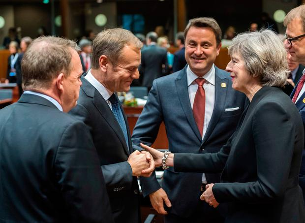 European Council President Donald Tusk, second left, shakes hands with British Prime Minister Theresa May during a round table meeting at an EU Summit in Brussels. (AP Photo/Geert Vanden Wijngaert)