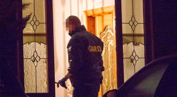 GardaI pictured searching a house in Tallaght