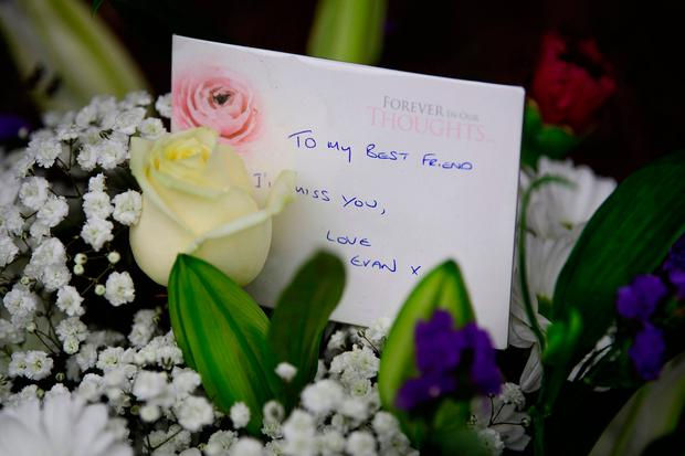 Flowers and a message left outside the house. Photo: Ben Cawthra/LNP