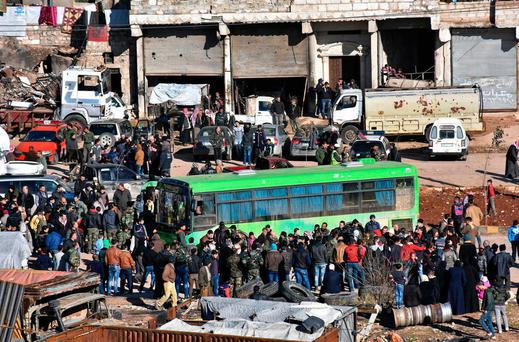 Residents gather near a green government bus for evacuating from eastern Aleppo. Photo: SANA via AP
