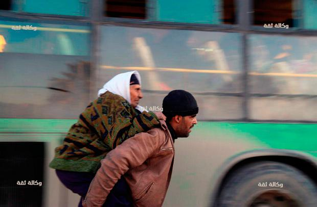 A Syrian man carrying an elderly woman to a bus for evacuation from eastern Aleppo, Syria. Photo: Thiqa News via AP