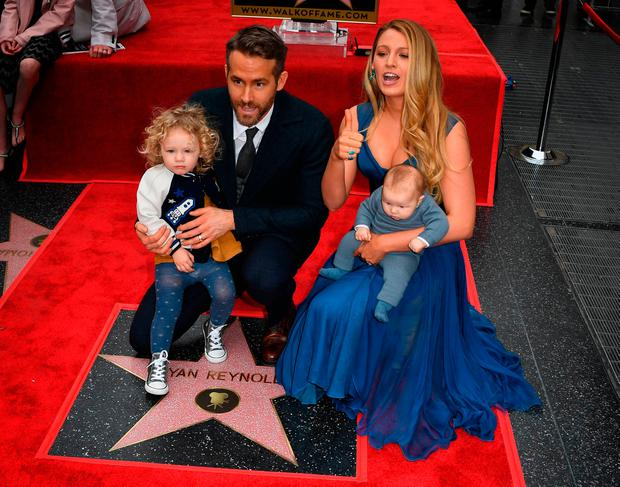 Actor Ryan Reynolds (2L) holds his daughter James as his wife Blake Lively holds their unnamed new baby during the Deadpool actors Hollywood Walk of Fame ceremony
