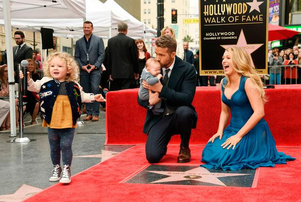 Ryan Reynolds' daughter James, left, steals the microphone as Reynolds poses with his wife, actress Blake Lively, and their youngest daughter during a ceremony to award him a star on the Hollywood Walk of Fame