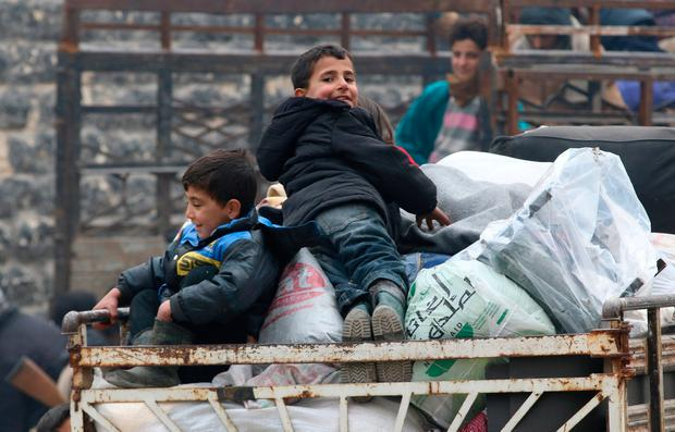 Boys react as they sit on belongings and wait to be evacuated from a rebel-held sector of eastern Aleppo. Photo: Reuters