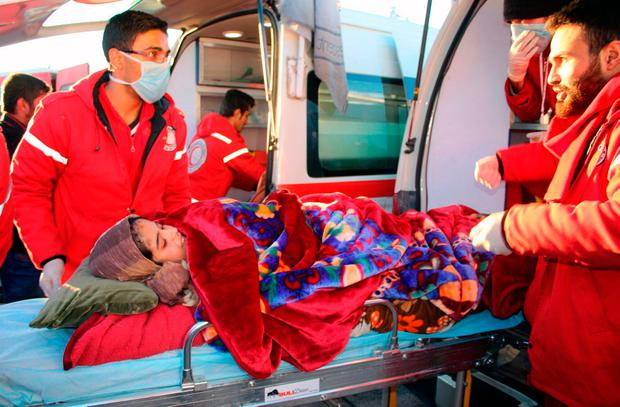 Members of the Syrian Arab Red Crescent carrying a girl on stretcher, while arriving in western rural Aleppo. Photo: AP
