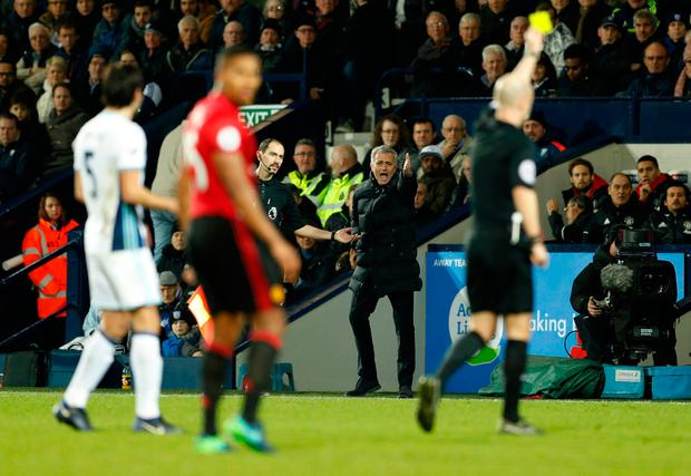 Manchester United manager Jose Mourinho reacts as referee Anthony Taylor shows a yellow card