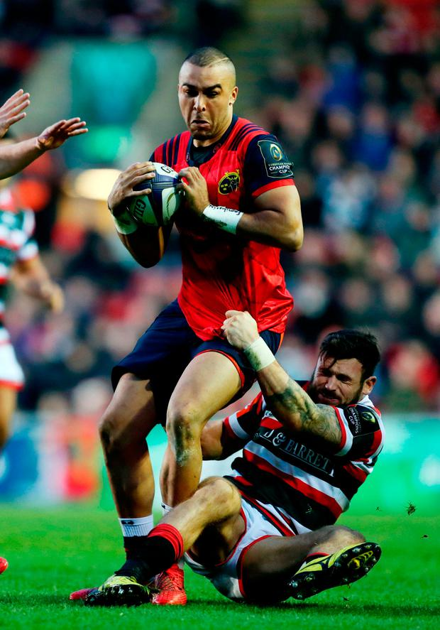 Munster's Simon Zebo is tackled by Leicester Tigers's Adam Thompstone during the European Champions Cup match at Welford Road, Leicester. Photo: David Davies/PA