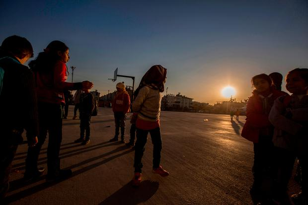 SAFE FROM SLAUGHTER: Children gather to play games in a makeshift playground, a reprieve from the barbarity of the Syrian civil war