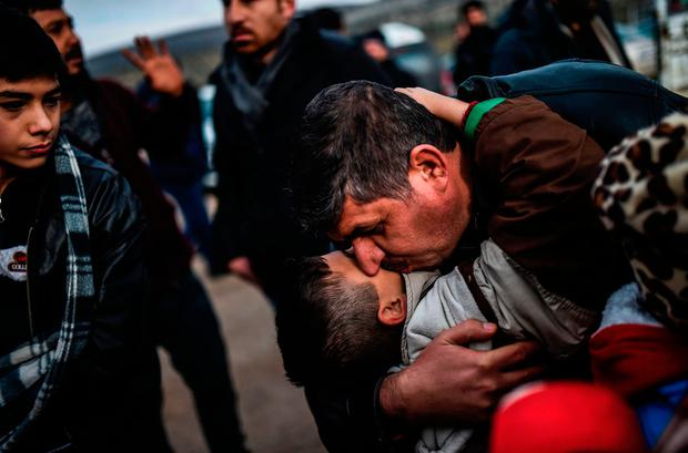 SAFE AT LAST: Syrian father Ali embraces one of his children upon their arrival at Turkish crossing gate of Cilvegozu