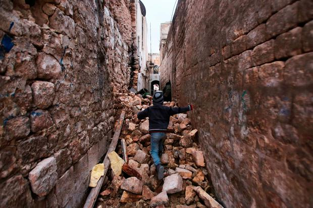 RUNNING THE GAUNTLET: Syrian boy makes his way through the rubble to his house in Aleppo's Dahret Awad neighbourhoodin