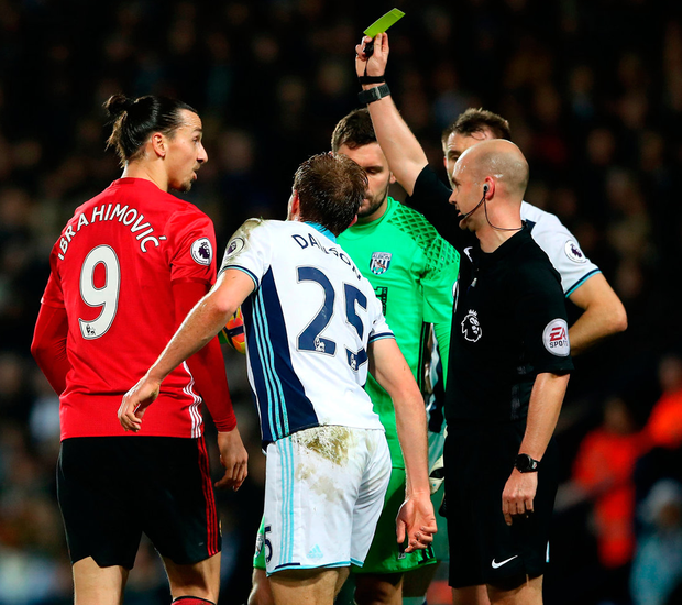 Manchester United's Zlatan Ibrahimovic (left) is shown a yellow card by referee Anthony Tayor after fouling West Bromwich Albion's Craig Dawson. Photo: Nick Potts/PA