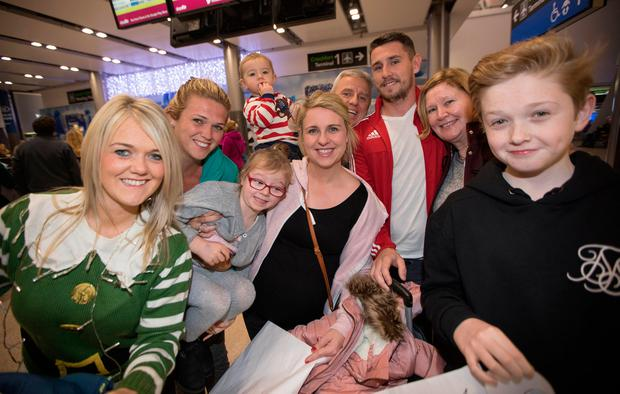Stephen Garbutt (red top) and Roxanne McAdam (pink top), who flew into Dublin airport from Australia for the Christmas holidays, are welcomed home by family members. Photo: Fergal Phillips